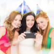 Three smiling women in hats having fun with camera — Stock Photo