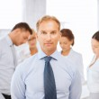 Businessman in office with group on the back — Stock Photo #35431939