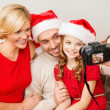 Smiling family in santa helper hats taking picture — Stock Photo #35433067