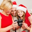 Family in santa helper hats looking at pictires — Stock Photo #35433093