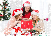 Women in santa helper hats with card and gifts — Stock Photo