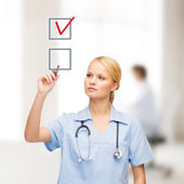 Doctor or nurse with marker drawning red checkmark — Stock Photo