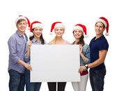 Group of smiling students with white blank board — Stock Photo