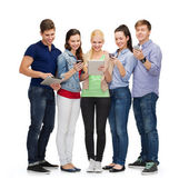 Smiling students using smartphones and tablet pc — Stok fotoğraf