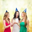 Three women wearing hats with champagne glasses — Стоковая фотография