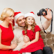Smiling family in santa helper hats taking picture — Stock Photo #35683221