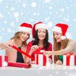Smiling women in santa helper hats with gift boxes — Foto de Stock