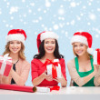 Stock Photo: Smiling women in santa helper hats with gift boxes