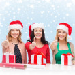 Smiling women in santa helper hats with gift boxes — Stock Photo