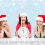 Women in santa helper hats with clock showing 12 — Stock Photo #35797003