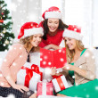 Women in santa helper hats with card and gifts — Стоковая фотография
