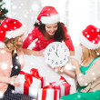 Women in santa helper hats with clock showing 12 — Stockfoto