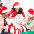 Women in santa helper hats with clock showing 12 — Stock Photo