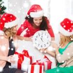 Women in santa helper hats with clock showing 12 — Stock Photo #35797193