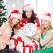 Women in santa helper hats with clock showing 12 — Stock fotografie