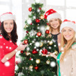 Women in santa helper hats decorating a tree — Stock Photo #35797267