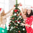 Women in santa helper hats decorating a tree — Stock Photo #35797305
