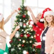 Women in santa helper hats decorating a tree — Stock Photo