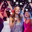 Three smiling women dancing and singing karaoke — Stock Photo