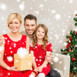 Smiling family holding gift box — Foto Stock