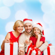Smiling family holding gift boxes and sparkles — Stock Photo #35798777