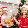 Smiling family decorating christmas tree — Stockfoto