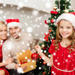 Smiling family decorating christmas tree — ストック写真