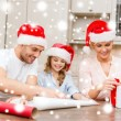 Smiling family in santa helper hats with gift box — Stok fotoğraf