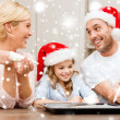 Happy family in santa helper hats making cookies — Foto Stock