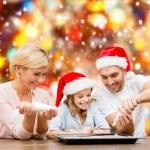 Happy family in santa helper hats making cookies — Stock Photo #35799285