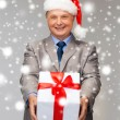 Smiling man in suit and santa helper hat with gift — Foto Stock