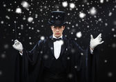 Magician in top hat with magic wand showing trick — Stock Photo
