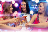 Three smiling women with cocktails in club — Stock Photo