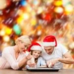 Happy family in santa helper hats making cookies — Stock Photo #35825633