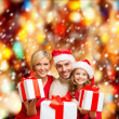 Stock Photo: Smiling family giving many gift boxes