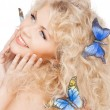 Happy woman with butterflies in hair — Stock Photo
