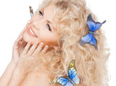 Happy woman with butterflies in hair — Photo