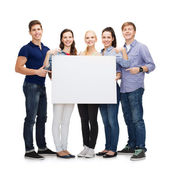 Group of smiling students with white blank board — Stok fotoğraf