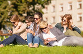 Students looking at smartphones and tablet pc — Foto Stock