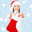 Smiling woman with small giftbox and stocking — Stock Photo