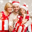 Smiling family holding gift boxes and sparkles — Stok fotoğraf