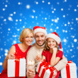 Smiling family holding gift boxes and sparkles — Stockfoto