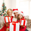 Smiling family giving many gift boxes — Stock Photo #35897411