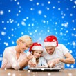 Happy family in santa helper hats making cookies — Stock fotografie