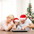 Happy family in santa helper hats making cookies — Stock Photo #35897441