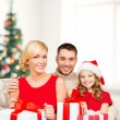 Smiling family holding many gift boxes — Stockfoto