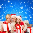 Smiling family holding gift boxes and sparkles — Lizenzfreies Foto