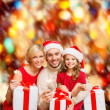 Stock Photo: Smiling family holding gift boxes and sparkles