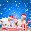Smiling family in santa helper hats with gift box — Stock Photo #35897491