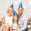 Happy family in hats celebrating — Stok fotoğraf